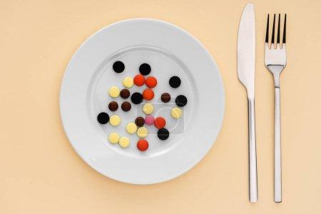 Photo pour Vue de dessus de fourchette, couteau et assiette avec diverses pilules sur fond beige - image libre de droit