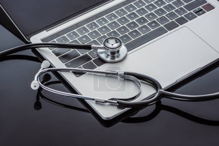 close up view of stethoscope and laptop on glass surface