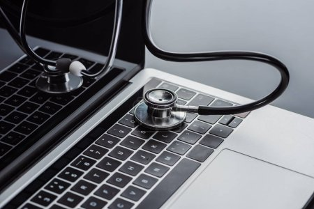 selective focus of stethoscope and laptop with blank screen on grey surface