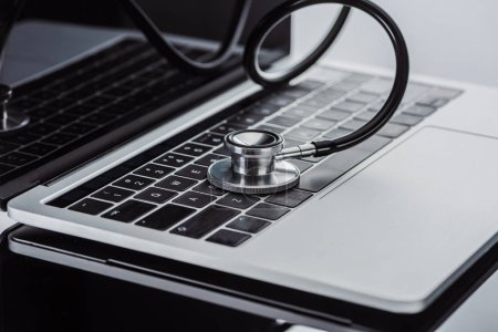 selective focus of stethoscope and laptop on blurred background
