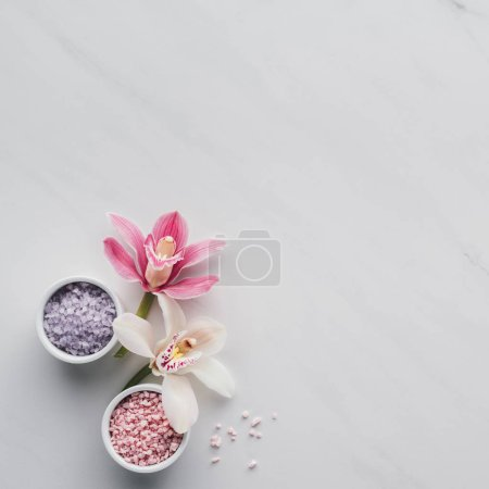 Photo pour Vue de dessus de belles fleurs d'orchidée et sel de mer dans des bols sur fond blanc - image libre de droit