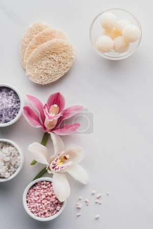 beautiful orchid flowers, sea salt in bowls and sponges on white background