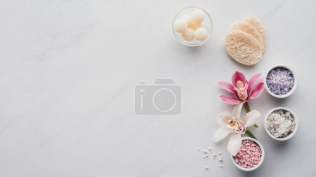 top view of beautiful orchid flowers, sea salt in bowls and sponges on white background