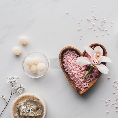top view of white orchid flower and pink sea salt in heart shaped bowl on white