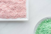 top view of pink and green sea salt on white background