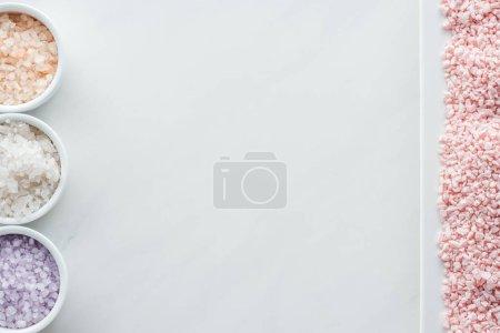 Foto de Vista superior de rosa sal y cuencos con sal de mar colorido sobre fondo blanco - Imagen libre de derechos