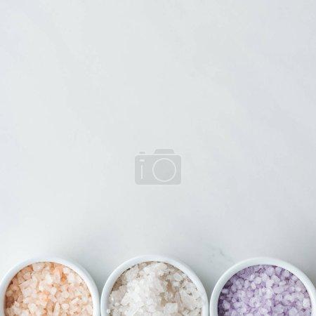 Foto de Vista superior de sal de mar colorido en tazones sobre fondo blanco - Imagen libre de derechos