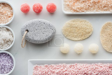 top view of various sea salt, sponges and handmade soap on white