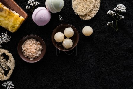 top view of handmade scrub, sea salt and small white flowers on black background