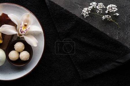 top view of beautiful white flowers, homemade scrub and black towel, spa treatment concept