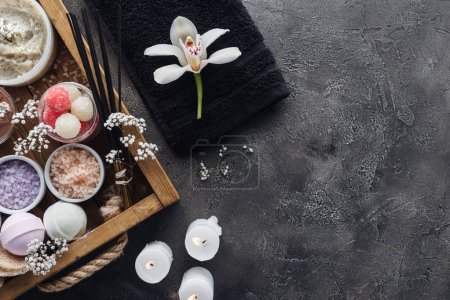 top view of beautiful orchid, towel, burning candles and spa accessories on grey background