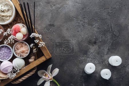 top view of spa and bath accessories in wooden box, orchid and candles on grey background