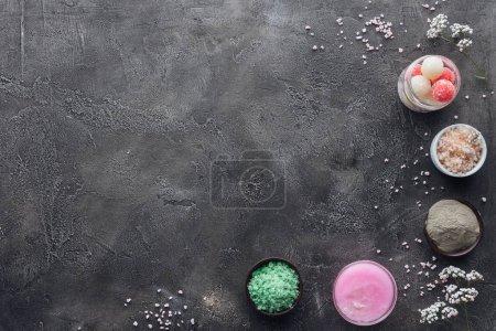 top view of handmade scrub, cream and sea salt on grey background