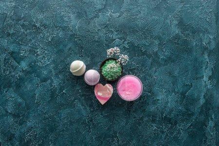 vue de dessus de sel de mer vert, belles petites fleurs et savons faits à la main sur fond de grunge