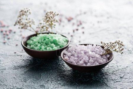 Photo pour Vue rapprochée du sel de mer dans les bols et les petites fleurs blanches - image libre de droit