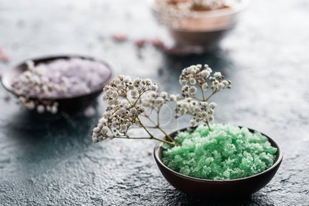 close-up view of sea salt in bowls and small white flowers, selective focus