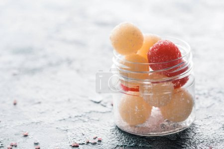 Close-up view of homemade scrub balls in glass container on grey