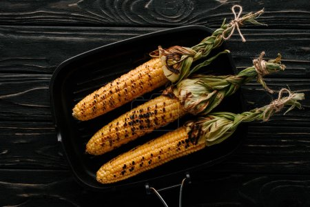 top view of delicious grilled corn on griddle pan on wooden table