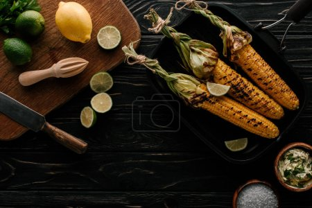 top view of cutting board with lime slices, lemon, cream with parsley, squeezer, knife near griddle pan with grilled corn on wooden table