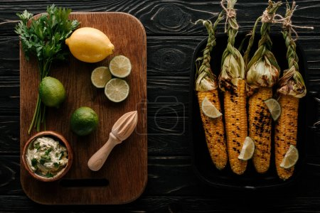 top view of cutting board with lime slices, lemon, cream with parsley, squeezer near griddle pan with grilled corn on wooden table