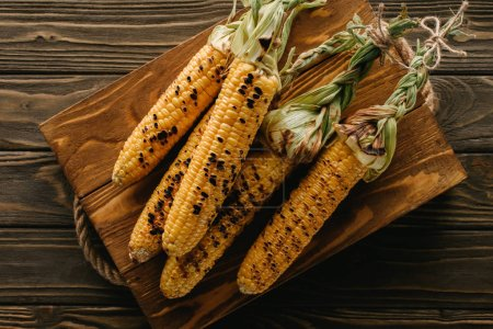 elevated view of delicious grilled corn on cutting board on wooden table