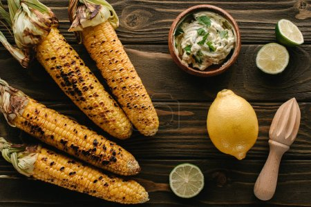 Photo for Top view of grilled corn, lime slices, lemon, wooden squeezer and cream with parsley on wooden table - Royalty Free Image