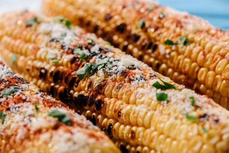 selective focus of delicious grilled corn with salt, parsley and chili spice