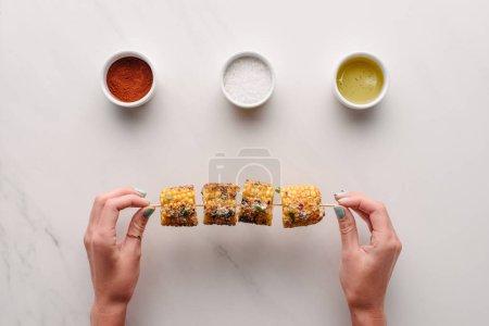 Photo pour Cropped image de femme tenant le maïs grillé sur la table de marbre avec du sel, huile et piment épice - image libre de droit