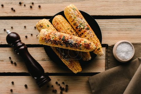 Photo for Top view of grilled corn, pepper grinder and salt on wooden table - Royalty Free Image
