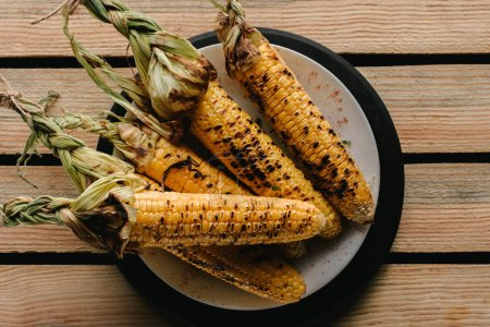 top view of delicious grilled corn on plate on wooden table