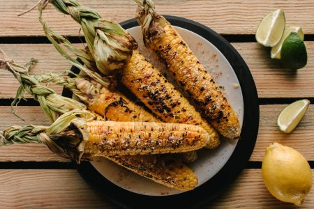 top view of delicious grilled corn on plate and lime slices with lemon on wooden table