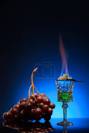 glass of flaming absinthe with sugar and grapes on dark blue background