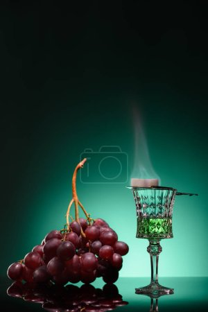 glass of burning absinthe with sugar and grapes on dark blue background