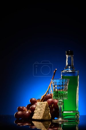 close-up shot of absinthe with grapes and dorblu cheese on mirror surface on dark blue background