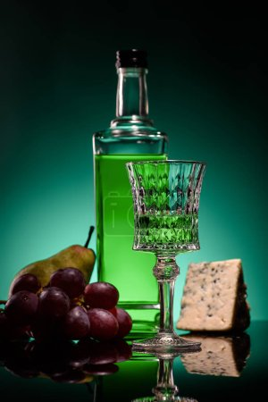 close-up shot of absinthe with ripe fruits and cheese on mirror surface on dark blue background