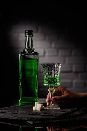 cropped shot of woman holding glass of absinthe on dark brick wall background