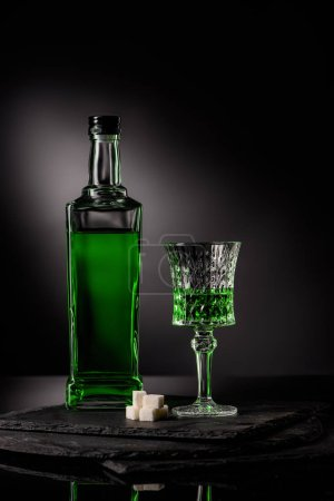 close-up shot of glass and bottle of absinthe with sugar cubes on dark background