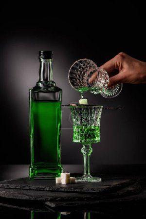 cropped shot of woman pouring absinthe in glass and on sugar cube on dark background