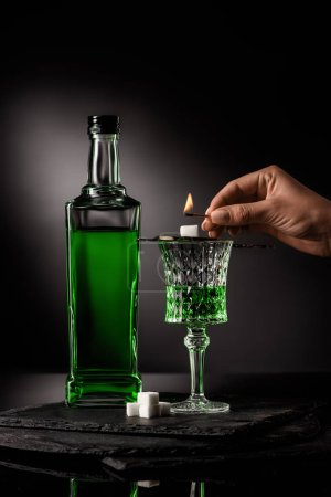 cropped shot of woman holding match over spoon with sugar cube on absinthe glass on dark background
