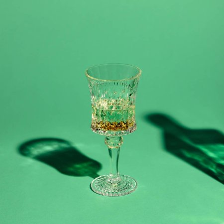 close-up shot of crystal glass of absinthe on green surface