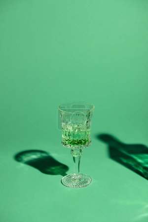 close-up shot of lead glass of absinthe on green surface