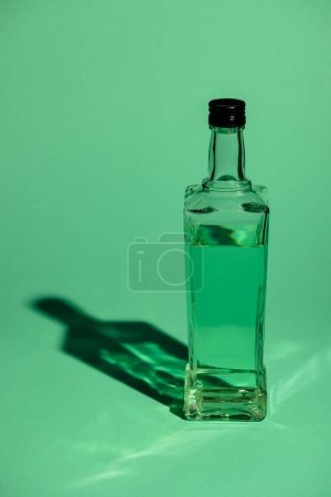 glass bottle of absinthe on green surface