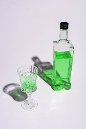 crystal glass and bottle of absinthe on white