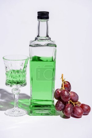 crystal glass and bottle of absinthe with branch of grapes on white