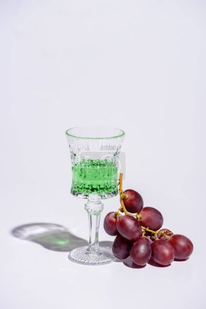 crystal glass of absinthe with branch of grapes on white