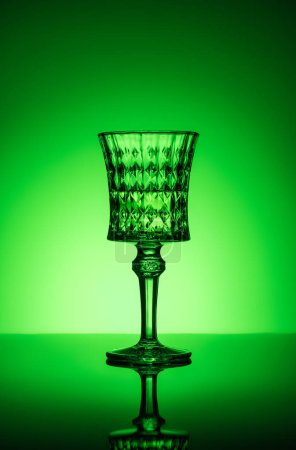 crystal glass of absinthe on reflective surface and dark green background