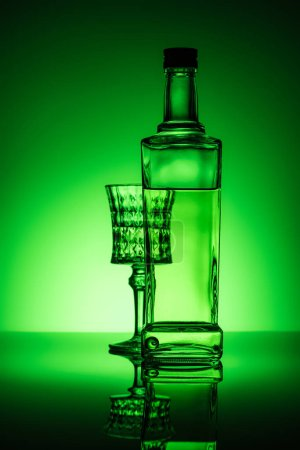 bottle of absinthe with lead glass on mirror surface and dark green background