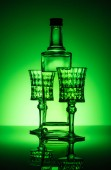 bottle of absinthe with lead glasses on mirror surface and dark green background