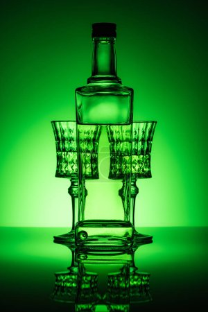 bottle of absinthe with crystal glasses on mirror surface and dark green background