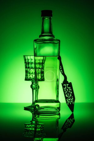 absinthe bottle with crystal glass and spoon on reflective surface and dark green background